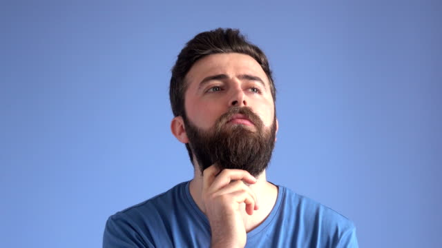 facial expression of thinking adult man on blue background - selimaksan stock videos & royalty-free footage