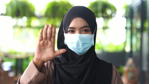 vídeos y material grabado en eventos de stock de expresión facial , joven mujer musulmana asiática con protección de máscara quirúrgica, parada, no, rechazo, mal estado, corte - alto descripción física