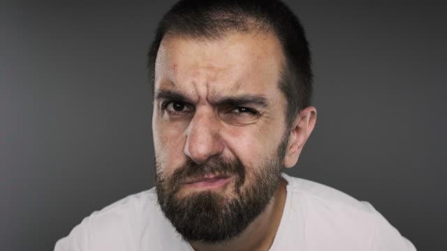 stockvideo's en b-roll-footage met de jonge mens van het gezichtsbehandeling op grijze achtergrond - ongeloof