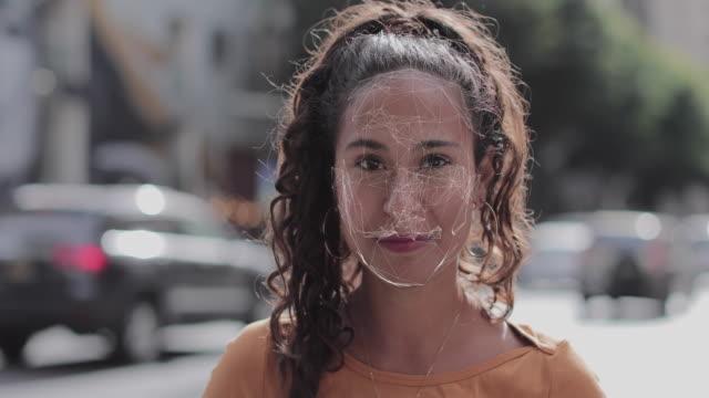vídeos de stock e filmes b-roll de facial recognition technology scanning identity of hispanic female on city road - documento