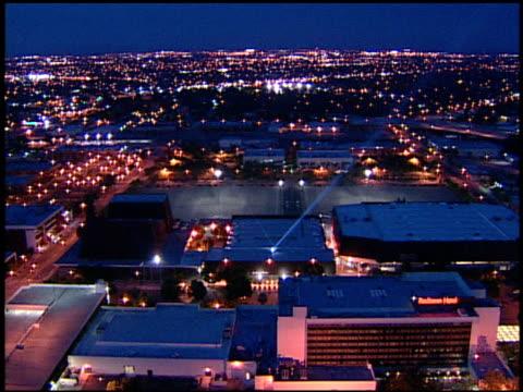 vídeos de stock, filmes e b-roll de flying around lit selland arena building empty parking lot fresno city traffic lights stretching in bg ca - fresno