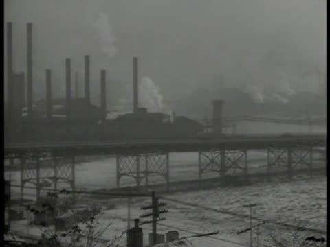 factories along river ws industrial factory w/ smoke stacks ext men moving furniture into building 'steel workers union hq' vs man w/ hat amp pipe... - gewerkschaft stock-videos und b-roll-filmmaterial