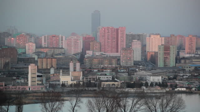 Factories and apartment buildings line the Taeong River in the city center of Pyongyang, North Korea.