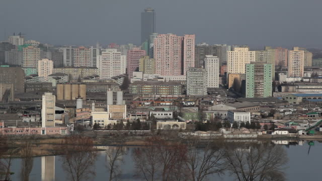 factories and apartment buildings tower over the taedong river in pyongyang. - pyongyang stock videos and b-roll footage