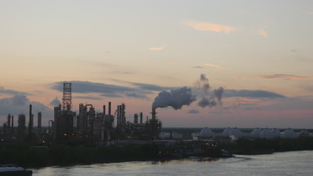 factory and smoke at sunset by the river - schornstein konstruktion stock-videos und b-roll-filmmaterial