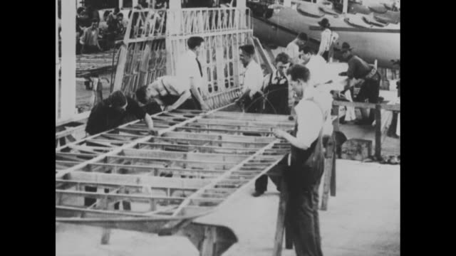 VS INT factory as workmen touch up the wooden framework of an airplane wing fuselages can be seen behind / workers with fuselages and other equipment...