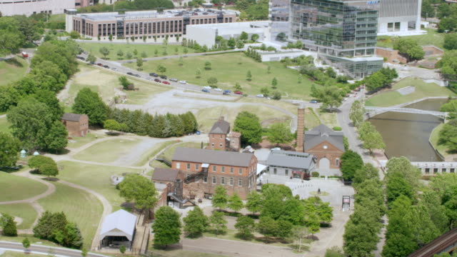 ws zo aerial pov factory building of historic tredegar iron works with commercial sign, modern downtown in background / richmond, virginia, united states - バージニア州 リッチモンド点の映像素材/bロール