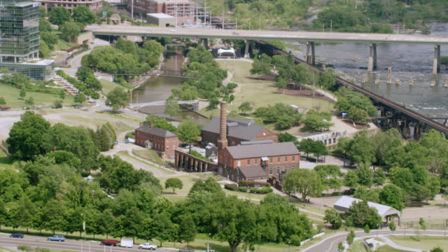 ws aerial pov factory building of historic tredegar iron works with james river and bridge / richmond, virginia, united states - richmond virginia stock videos & royalty-free footage
