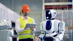 Factory employee is communicating with a humanoid in gestures