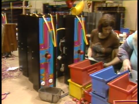 Factory employees soldering wires in Ms PacMan game