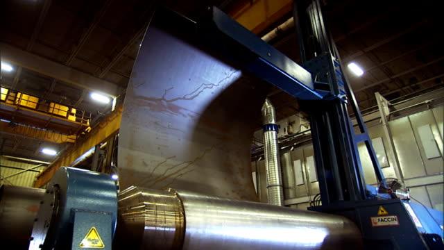 a factory machine rolls sheet metal onto a lift. - sheet metal stock videos and b-roll footage