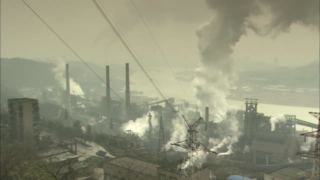 factory on the riverbank and rising smoke;   tilt up   rising smoke.  close shot chongqing, sichuan province - luftverschmutzung stock-videos und b-roll-filmmaterial
