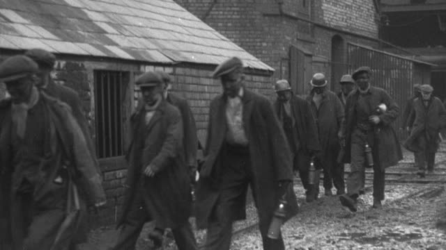 stockvideo's en b-roll-footage met montage factory production grinding to a halt, workers abandoning facilities, and the gates being closed behind them / united kingdom - 1937
