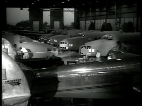 factory smoke stacks. int airplanes under construction in hangar. engineers working on airplane nose. vs man drilling single engine wing. wwii - weaponry stock videos & royalty-free footage