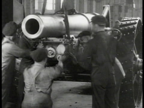 factory smoke stacks. int factory workers fitting piece of cannon. men working on large bomb shell. workers pushing carts of rifles into factory. ext... - waffe stock-videos und b-roll-filmmaterial