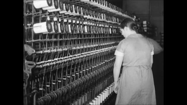 factory smoke stacks int ms woman looking at fabric looms vs factory men at machines working women working w/ spools men working on cotton winding... - webstuhl stock-videos und b-roll-filmmaterial