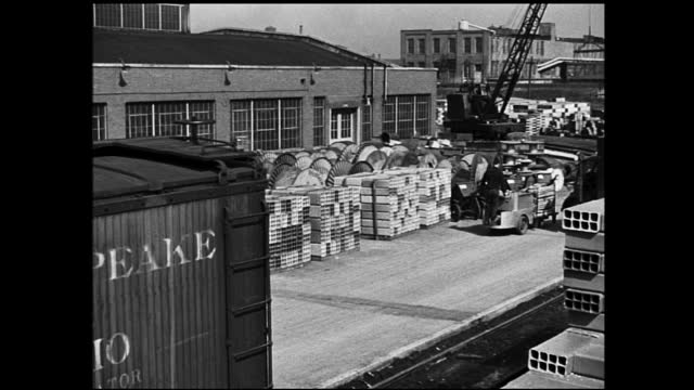 vídeos y material grabado en eventos de stock de factory stockyard, worker with forklift passing by and large crane in the background - 1940 1949