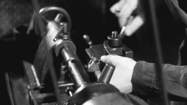 1941 montage factory trainee setting up and lubricating lathe / united kingdom - 製造工場点の映像素材/bロール