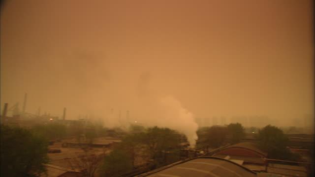 ws pan factory under overcast sky, beijing, china - スモッグ点の映像素材/bロール