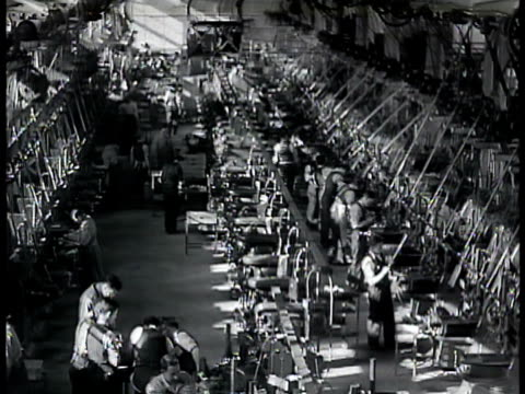 factory w/ filled parking lot int factory workers at machines tank moving on crane over other tanks men polishing steel shell casings workers leaving... - costruttore navale video stock e b–roll