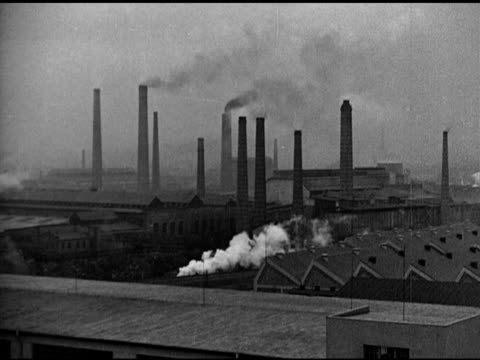 vídeos y material grabado en eventos de stock de factory w/ many smokestacks train moving between buildings int factory w/ men working on torpedoes bomber aircraft bodies - munición