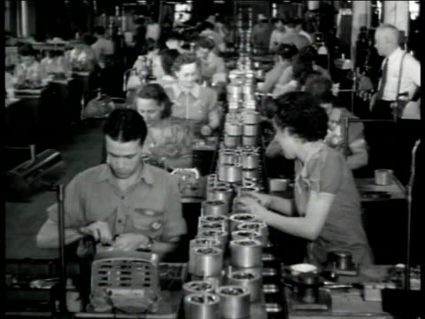 Factory w/ people at tables working on parts People working on parts along assembly line Automatic pilot on tilting machine Cluster of airplane...