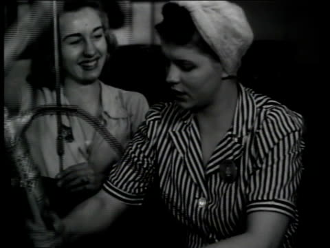 Factory women workers using machines Woman screwing top on airplane part Two women one smoking cigarette working talking at table filled w/ parts