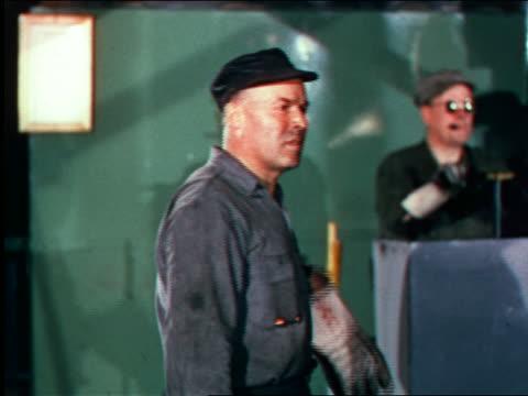 1946 factory worker bending down to look at something / industrial - 1946 bildbanksvideor och videomaterial från bakom kulisserna