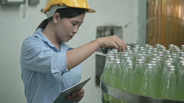 vídeos de stock, filmes e b-roll de operário da fábrica verificando as garrafas em fila na esteira transportadora - caderno de anotação