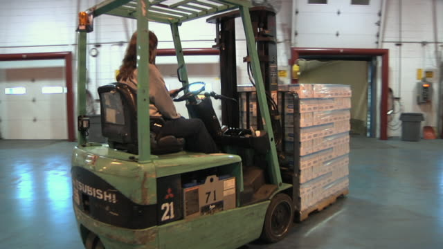 WS MS PAN Factory worker driving forklift with boxes into loading dock, Chelsea, Michigan, USA
