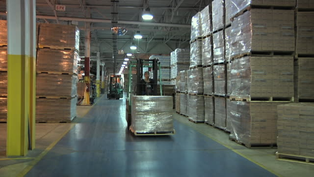 WS MS Factory worker driving forklift with boxes through warehouse, Chelsea, Michigan, USA