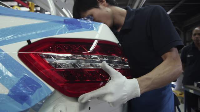 cu factory worker installing tail light on car on production line / samut prakan, bang muang mai, thailand - nur junge männer stock-videos und b-roll-filmmaterial