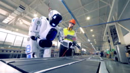 Factory worker is regulating robot's settings by remote control during working process