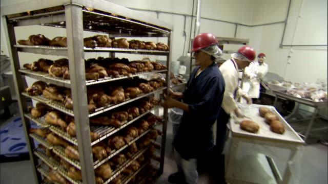 vídeos de stock e filmes b-roll de a factory worker pushes a cart of processed turkey meat. - bata cirúrgica