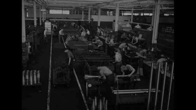vidéos et rushes de factory worker pushes cart of pipes though stacks of poles with men at work stations / vs men at work stations / man wheels muzzle of artillery gun... - armement