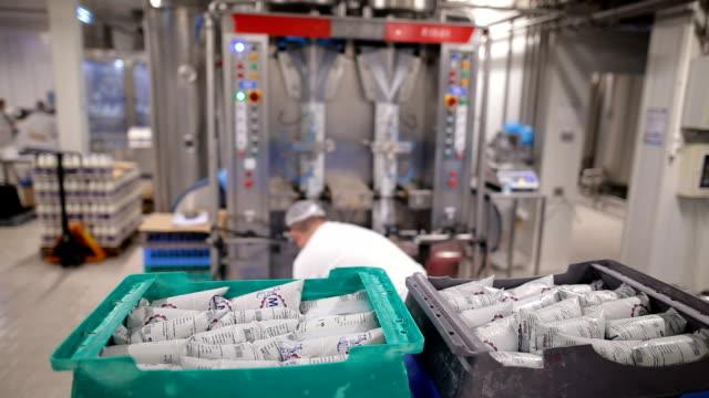 vídeos y material grabado en eventos de stock de trabajador de la fábrica reciben bolsas de leche para la entrega - embalaje