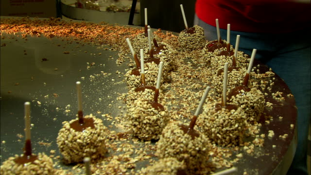a factory worker removes caramel apples from a rotating machine. - toffee stock videos & royalty-free footage