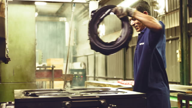 Factory worker removing the Semi-finished product from the hot press machine
