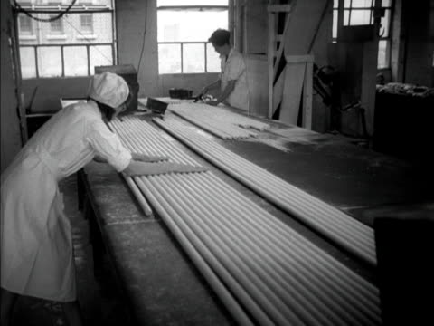 a factory worker rolls long sections of sugar rock while a fan helps to dry the mixture 1951 - dondolarsi video stock e b–roll