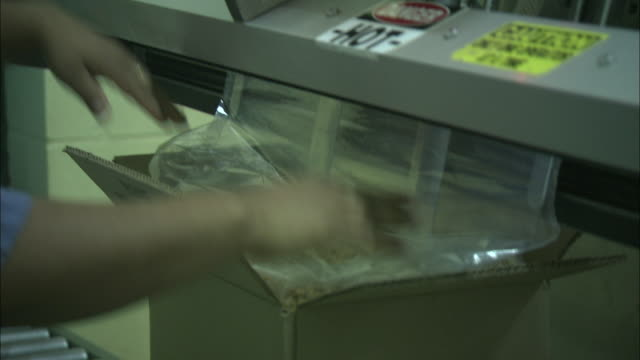 stockvideo's en b-roll-footage met a factory worker seals peanuts in a plastic bag and cardboard box. - noot