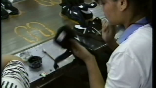 ZI Factory worker touching up sneakers with black paint on a Nike assembly line / Shanghai China