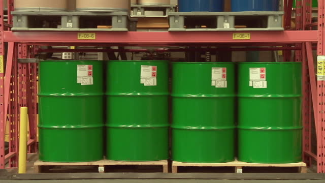 MS Factory worker walking by four green oil drums on factory floor / Rathdum, Ireland