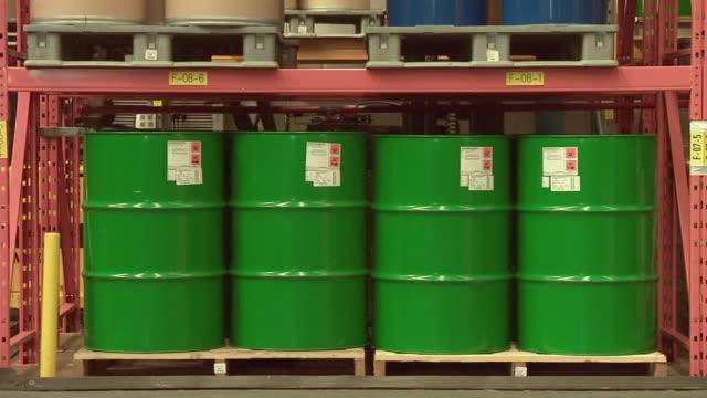 vídeos de stock, filmes e b-roll de ms factory worker walking by four green oil drums on factory floor / rathdum, ireland - barril