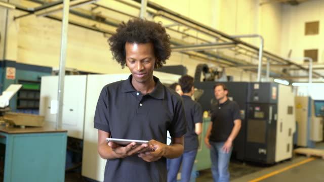 vidéos et rushes de ouvrier d'usine avec la tablette numérique sur l'étage d'atelier - apprenti