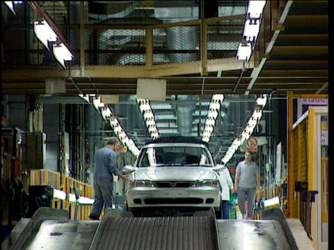 Factory workers add finishing touches to cars that roll off production line