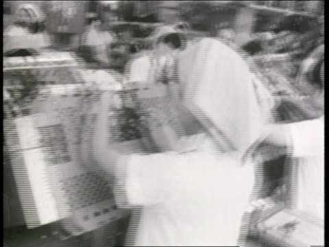factory workers assemble televisions at a sony plant in japan - 1960 stock-videos und b-roll-filmmaterial