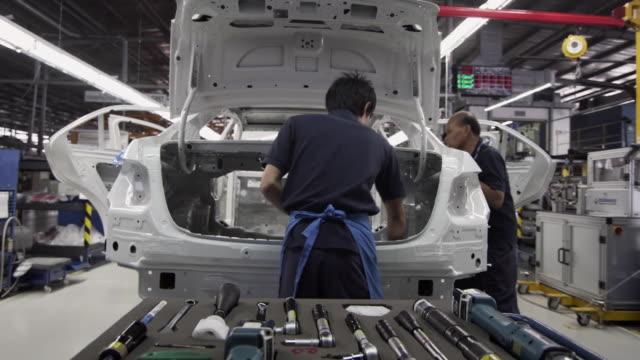 vídeos y material grabado en eventos de stock de ms factory workers assembling car on production line / samut prakan, bang muang mai, thailand - fábrica de coches