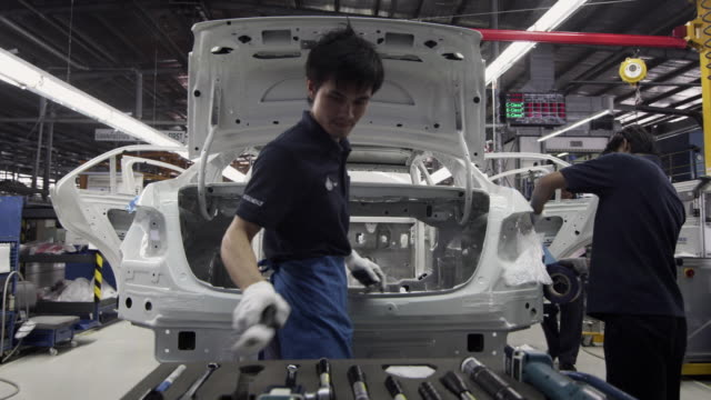 stockvideo's en b-roll-footage met ms factory workers assembling car on production line / samut prakan, bang muang mai, thailand - autofabriek