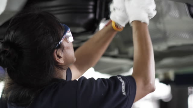 vídeos de stock e filmes b-roll de cu pan factory workers assembling car on production line / samut prakan, bang muang mai, thailand - profissão em fabrico