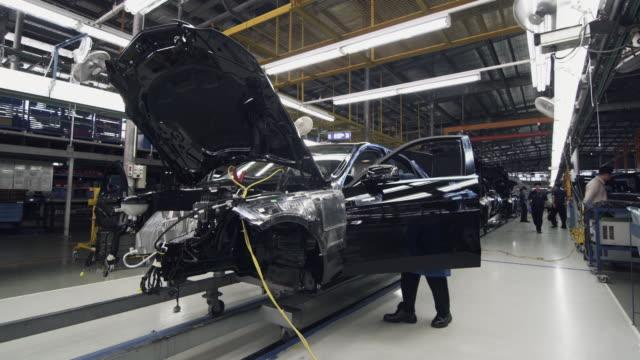 vídeos de stock, filmes e b-roll de ws factory workers assembling car on production line / samut prakan, bang muang mai, thailand - indústria automobilística